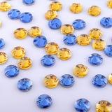 Beaucoup de pierres cousues jaunes et bleues rondes sur un fond blanc images stock