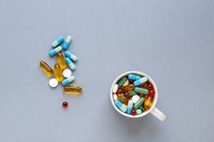 Beaucoup de pilules colorées dans la tasse sur le fond gris Photographie stock