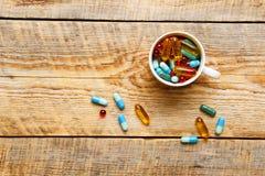 Beaucoup de pilules colorées dans la tasse wodden dessus la table Image stock