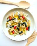 Beaucoup de pilules d'un plat blanc images stock