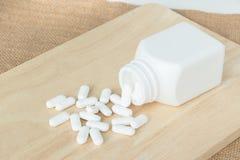 Beaucoup de pilules/de comprimés blancs/médecine du plat en bois Images stock