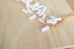 Beaucoup de pilules/de comprimés blancs/médecine du plat en bois Photos libres de droits