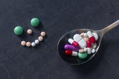 Beaucoup de pilules et d'étiquettes colorées avec la cuillère sur un fond foncé Pha Photos libres de droits