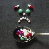 Beaucoup de pilules et d'étiquettes colorées avec la cuillère sur un fond foncé Pha Image libre de droits