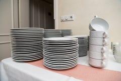 Beaucoup de plats modernes propres en céramique blancs sur une table Image libre de droits