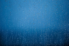 Beaucoup de pluie se laisse tomber sur un fond de bleu de fenêtre Photographie stock