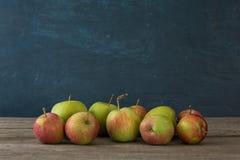Beaucoup de pommes sur la table en bois sur le fond bleu Images stock