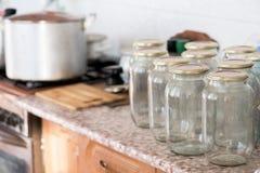 Beaucoup de pots en verre se tenant sur la table devant la préservation près de la cuisinière à gaz photos libres de droits