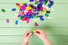 Beaucoup de puzzles sur la table en bois L'enfant relie des puzzles Images libres de droits