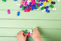 Beaucoup de puzzles sur la table en bois L'enfant relie des puzzles Photographie stock