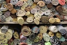 Beaucoup de rouleaux de tissus précieux sur les étagères du mercier Images stock