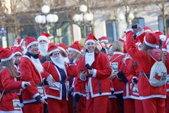 Beaucoup de Santa heureuses dans des robes rouges traditionnelles et barbe dans le St images libres de droits