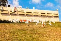 Beaucoup de signes ou de drapeaux abstraits de ondulation de mains installés sur une pelouse herbeuse Photographie stock libre de droits