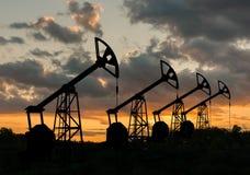 Beaucoup de silhouettes des plates-formes pétrolières de perçage au coucher du soleil Images stock