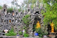 Beaucoup de statues de Bouddha sont mises dans l'abondance de petits trous dans un mur fait en coquillage dans une pagoda au Viet Images libres de droits
