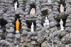 Beaucoup de statues de Bouddha sont mises dans l'abondance de petits trous dans un mur fait en coquillage dans une pagoda au Viet Images stock