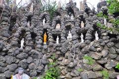 Beaucoup de statues de Bouddha sont mises dans l'abondance de petits trous dans un mur fait en coquillage dans une pagoda au Viet Photos libres de droits