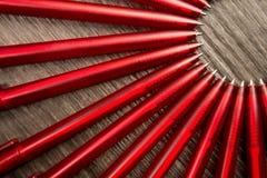 Beaucoup de stylos de rouge en cercle sur un fond en bois noir Concentré Photographie stock libre de droits