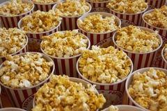 Beaucoup de tasses avec le maïs éclaté sur le contre- plan rapproché Photo stock