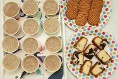 Beaucoup de tasses de thé chaud avec des biscuits et des gâteaux Images stock