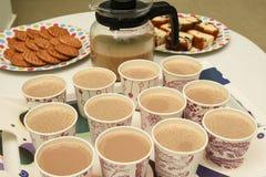 Beaucoup de tasses de thé chaud avec des biscuits et des gâteaux Photographie stock