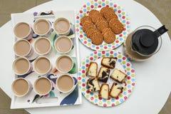 Beaucoup de tasses de thé chaud avec des biscuits et des gâteaux Image libre de droits