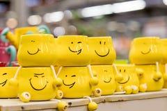 Beaucoup de tasses jaunes avec les visages drôles sur le fond brouillé Le concept d'une société amicale, une grande famille, réun photo stock