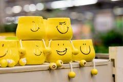 Beaucoup de tasses jaunes avec les visages drôles sur le fond brouillé Le concept d'une société amicale, une grande famille, réun image libre de droits