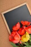 Beaucoup de tulipes rouges et jaunes s'ouvrent sur le tableau noir vide, au-dessus du liège b Photographie stock libre de droits