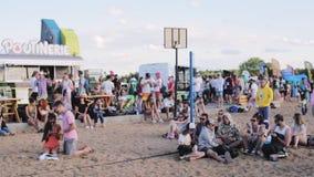 Beaucoup de types et de filles attirants s'asseyent sur le sable, entretien, plaisanterie, applaudissements, regard autour clips vidéos