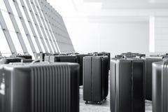 Beaucoup de valises noires se tenant dans un aéroport images stock