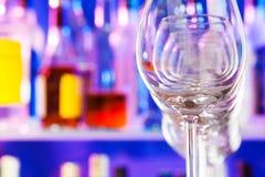 Beaucoup de verres transparents dans une rangée et des bouteilles de barre Images stock