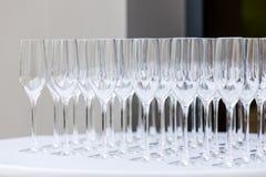 Beaucoup de verres de vin propres vides sur un fond clair Photographie stock