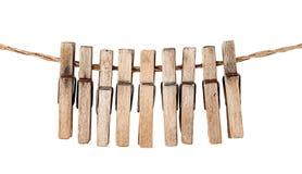 Beaucoup de vieilles pinces à linge en bois sur une corde d'isolement Image libre de droits