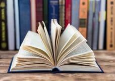 Beaucoup de vieux livres sur le fond en bois La source d'information Ouvrez le livre d'intérieur Bibliothèque à la maison La conn Photo libre de droits