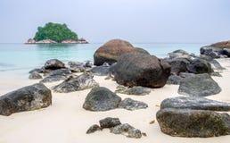 Beaucoup grande roche sur la mer blanche d'émeraude de sable Photographie stock
