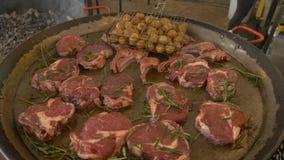 Beaucoup grands de morceaux crus et juteux frais de bifteck sont faits frire sur un gril de barbecue avec une jeune pomme de terr banque de vidéos