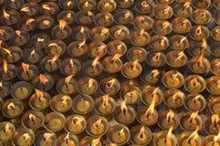 Beaucoup huile brûlante s'allumant vers le haut des lampes de bougies dans le temple bouddhiste - grand stupa Bodnath à Katmandou Photo stock