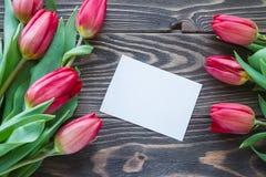 Beaucoup jaillissent les fleurs rouges avec la carte de voeux sur la table en bois Photos stock