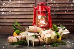 Beaucoup ont décoré les cadeaux de Noël et la vieille lampe à pétrole de vintage sur le fond en bois Image libre de droits