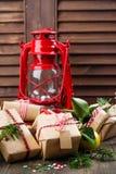 Beaucoup ont décoré les cadeaux de Noël et la vieille lampe à pétrole de vintage sur le fond en bois Photographie stock libre de droits