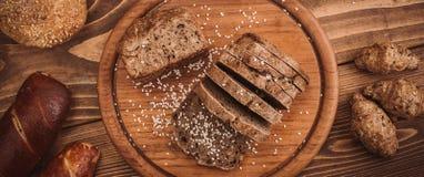 Beaucoup ont mélangé les pains et les petits pains cuits au four sur la table en bois rustique Photo libre de droits