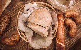 Beaucoup ont mélangé les pains et les petits pains cuits au four sur la table en bois rustique Images libres de droits