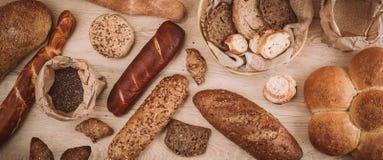 Beaucoup ont mélangé les pains et les petits pains cuits au four sur la table en bois rustique Photographie stock libre de droits