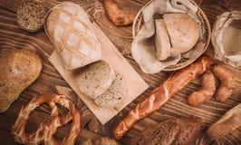 Beaucoup ont mélangé les pains et les petits pains cuits au four sur la table en bois rustique Image stock