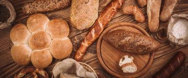 Beaucoup ont mélangé les pains et les petits pains cuits au four sur la table en bois rustique Photos stock