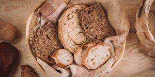 Beaucoup ont mélangé les pains et les petits pains cuits au four sur la table en bois rustique Image libre de droits