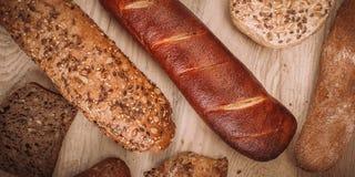Beaucoup ont mélangé les pains et les petits pains cuits au four sur la table en bois rustique Photos libres de droits