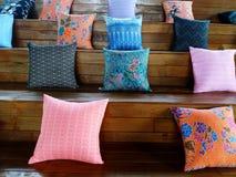 Beaucoup oreiller coloré mettant sur les escaliers en bois photos stock