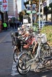 Beaucoup vont à vélo le parc au stationnement de bicyclette sur le trottoir près de la route chez Namba, Japon Images libres de droits